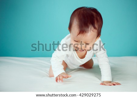 A crawling baby in diaper with blue background (soft focus on the eyes) - stock photo