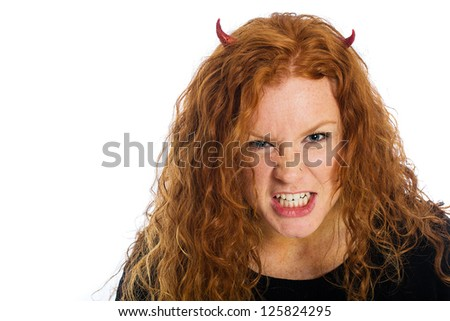 A crazy, angry woman with red hair and devil horns - stock photo