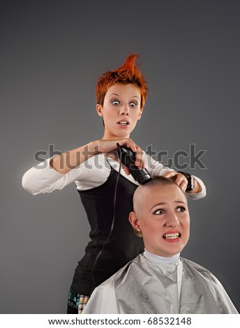 A crazy hairdresser shaves a girl off her hair - stock photo