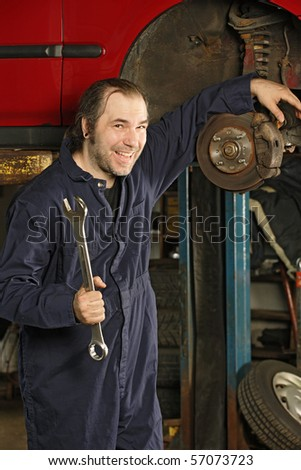 A crazy happy mechanic fixing brakes. - stock photo