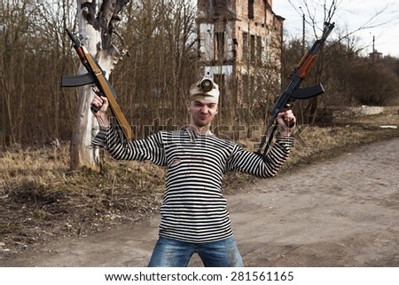 A crazy looking man with two guns - stock photo