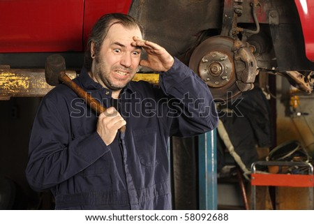 A crazy mechanic confused on what to do to fix the car. - stock photo