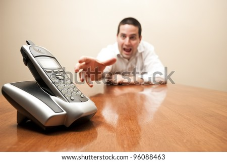 A crazy reaches for a modern cordless phone - stock photo
