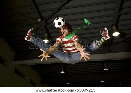 a crazy soccer or football fan flying in the air with a soccer ball