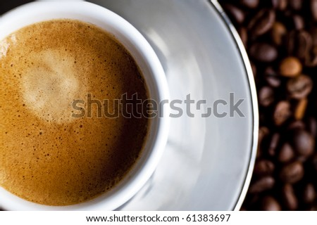 A creamy espresso on a bed of coffe beans - stock photo
