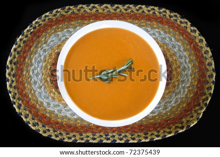 A creamy tomato basil bisque sits on a multicolored jute placemat. A sprig of rosemary garnishes the dish. - stock photo