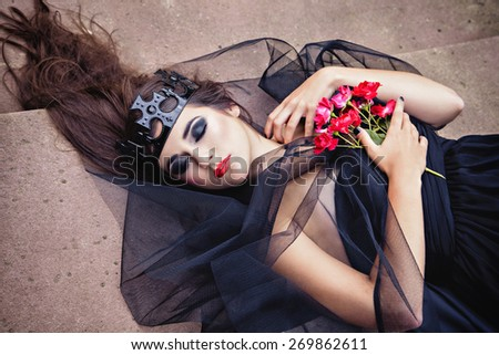 A creative photo of pretty brunette woman in black crown