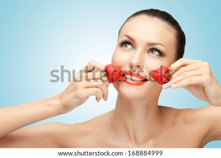 A creative portrait of a beautiful girl holding juicy strawberries near her lips with desire. - stock photo