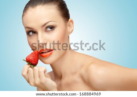 A creative portrait of a beautiful girl holding with one hand a juicy strawberry near her lips with temptation. - stock photo