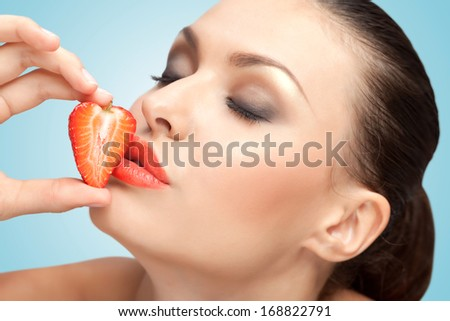 A creative portrait of a beautiful girl kissing a fresh strawberry with delicious red lips.