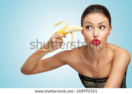 A creative portrait of a beautiful girl trying to shoot herself with a banana gun. - stock photo