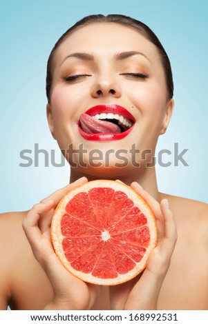 A creative portrait of a beautiful girl with a red grapefruit and a sexy tongue.