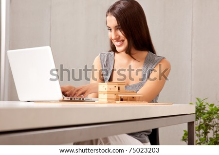 A creative professional woman working at a desk with a laptop and house model - stock photo