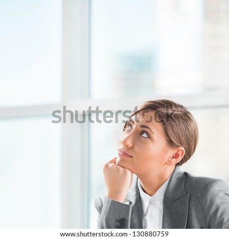 A creative young business woman looking away with hand on her chin - stock photo