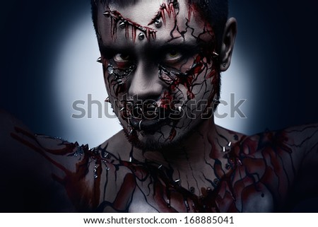 A creepy halloween concept of a dark angry moor with a peircing and bloody body art. - stock photo