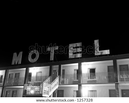 A creepy old motel sign in black and white. - stock photo