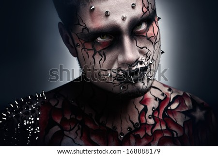 A creepy portrait of a pierced halloween moor with bloody body art.