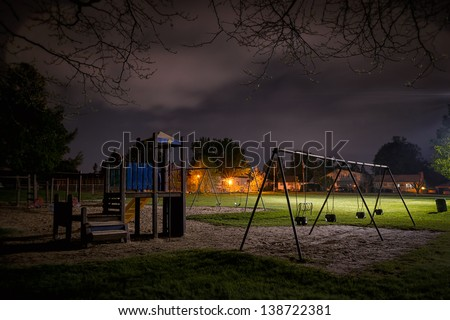 A creepy scene of a deserted children's playground in a suburban park at night time.