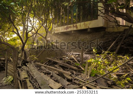 A creepy scenery, this abandoned woods creating a moody atmosphere along with the magnificent light. - stock photo