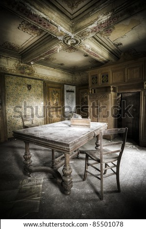 A creepy scenery, this old table and chair waiting for a person to take a seat. - stock photo
