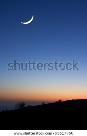 A crescent moon at sunset above silhouetted trees - stock photo