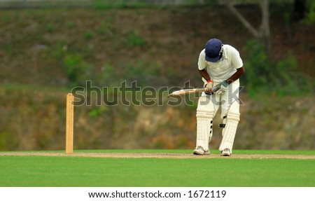 A cricket batsman getting ready to hit - stock photo