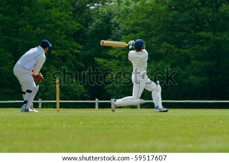 A cricket batsman playing a pull shot towards the boundary in a cricket match while the catcher looks on. - stock photo