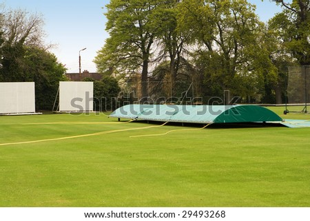 A cricket ground with covers on the pitch - stock photo