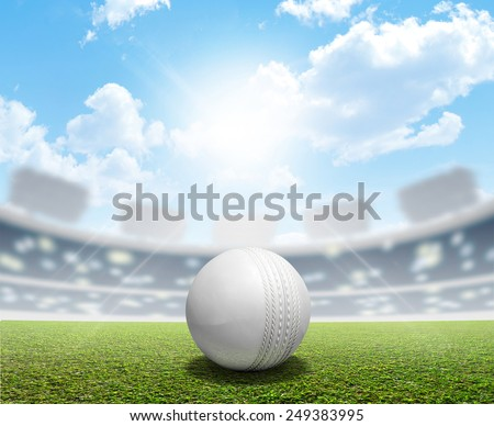 A cricket stadium with a white leather cricket ball on an unmarked green grass pitch in the daytime under a blue sky  - stock photo