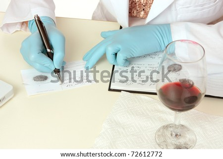 A crime scene forensic scientist obtains fingerprints from a glass using latent powder and tape and then writes down details.  Details are fictitious. - stock photo