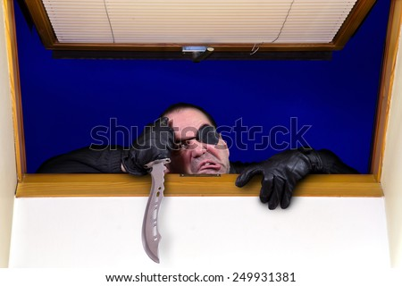 A criminal enters the house through the roof window  - stock photo