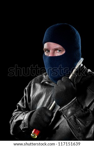 A criminal thief in a ski mask to hide his identity holds a large screwdriver as he prepared to commit a crime. - stock photo
