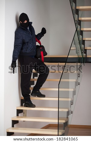 A criminal with a bag standing on a staircase - stock photo