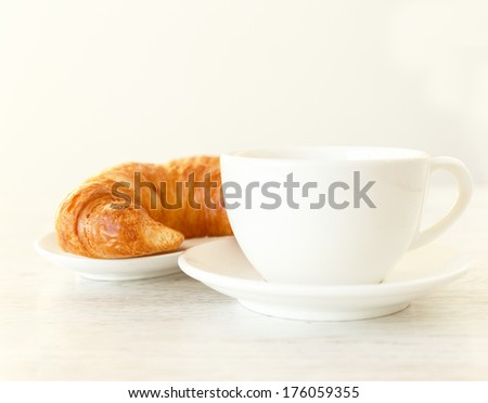 A croissant siding a cup of coffee