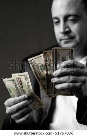A crooked looking man counting a handful of one hundred dollar bills. Shallow depth of field. - stock photo