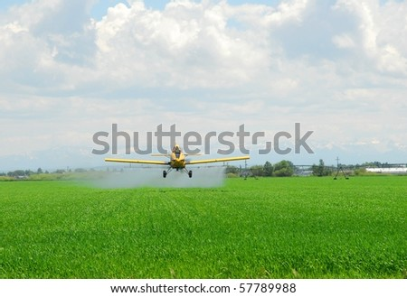 A crop duster applies chemicals to a field. - stock photo