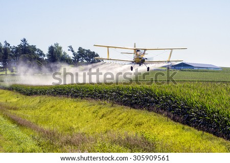 A crop duster applies chemicals to a field of vegetation. - stock photo