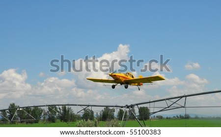 A crop duster finishes a pass down a field as it climbs over a farmer's irrigation system.