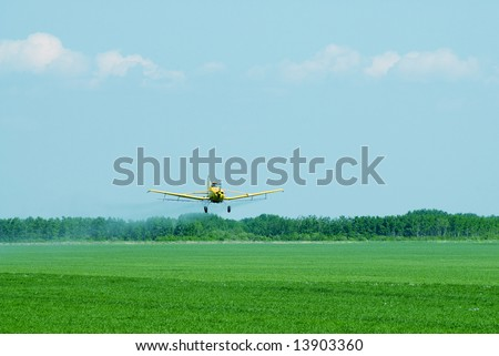 A crop duster spraying fertilizer and chemicals on a field - stock photo