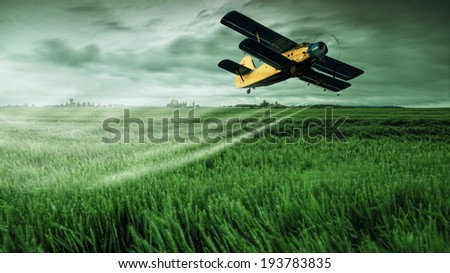 A crop dusting plane working over a field  - stock photo