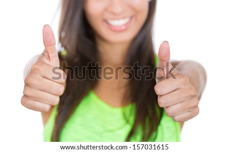 A cropped closeup image of a smiling, happy businesswoman or student giving us thumbs up, focus on hands - stock photo