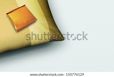 A cropped corner of a closeup of a tan colored pillow on a white fabric background with a complimentary gold foiled chocolate ontop of it - stock photo