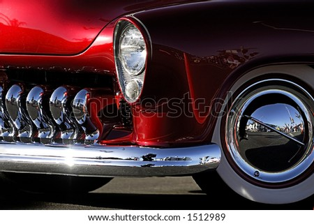 A cropped image of a fully restored classic old car with lots of shiny chrome. - stock photo