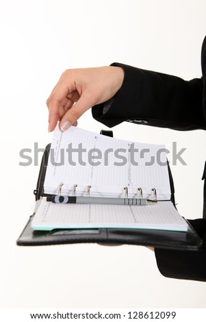 A cropped picture of a businesswoman holding  a planner.