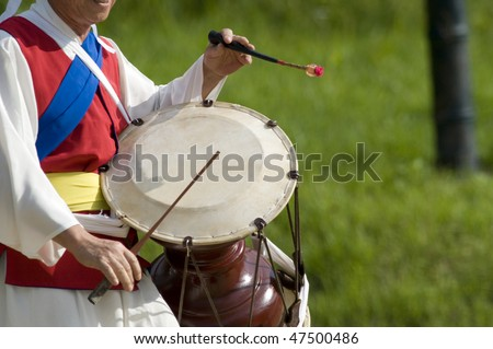 A cropped, side-view of a Korean drummer playing the traditional hourglass-shaped drum (janggu). - stock photo