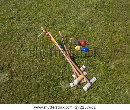 A croquet set. Four wooden mallets, four balls, two hoops on grass field - stock photo