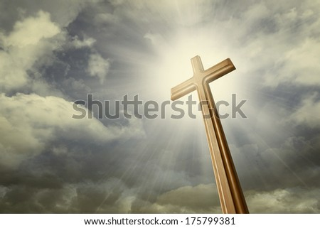 A cross against shining light on the sky