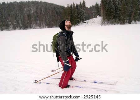 A cross country skiier looking like he is very tired. Humorous image. - stock photo