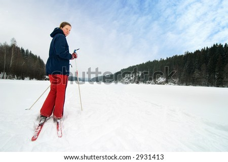 A cross country skiier out on a refreshing trip over a frozen lake. - stock photo