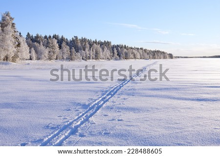 A cross-country track passes over a lake in sunshine. Forest and trees in snow and frost in the background.  - stock photo